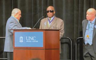 Vision impaired man speaking at a podium